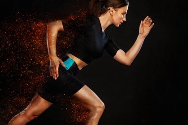 Sprinter and runner girl. Running concept. Fitness and sport motivation. Strong and fit athletic, woman sprinter or runner, running on black background in the fire wearing sportswear.