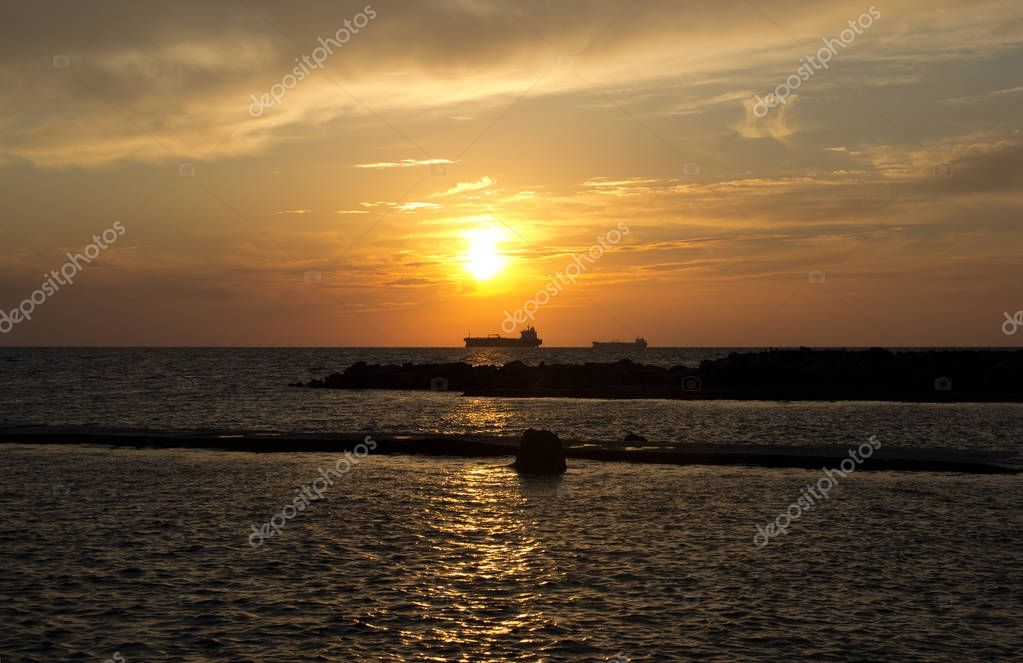 Sunset at sea and the silhouettes of two ships