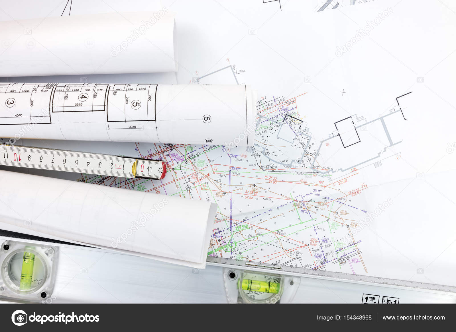 Spirit level and zigzag ruler with rolls of construction spirit level and zigzag ruler with rolls of construction blueprints on architect workplace stock photo pooptronica