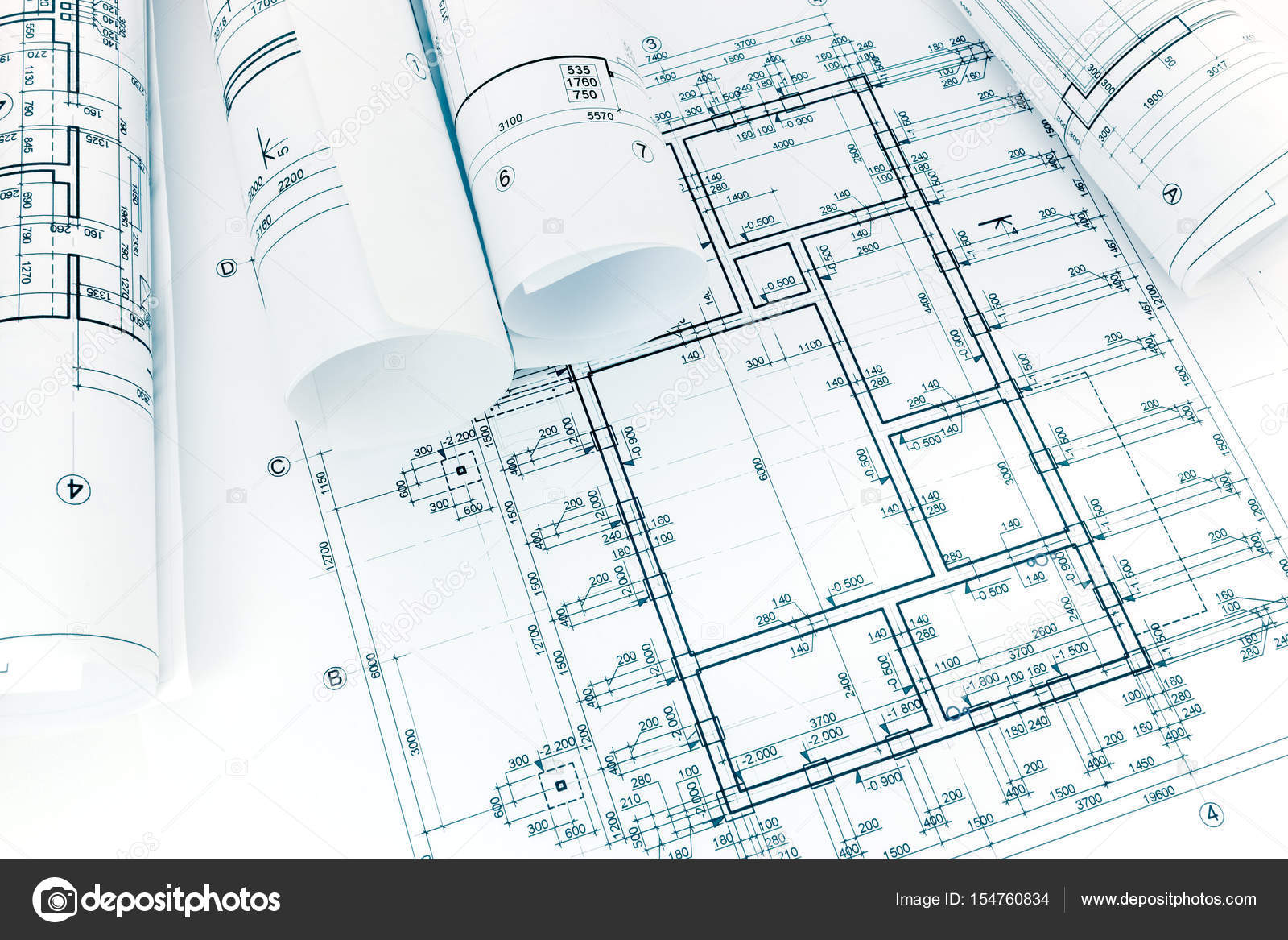 Rolled Building Plans On Architectural Blueprint Background Stock