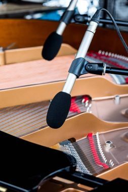 Microphones above grand piano with selective focus on one of the them
