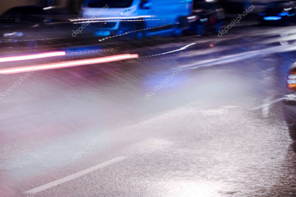 blurred red headlights of car driving on flooded night road during heavy rain