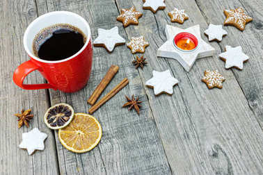 gingerbread cookies with spiced fruit and cup of coffee on grey wooden background