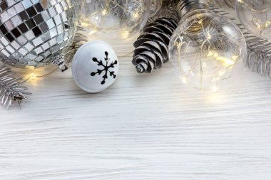 silver christmas tree branch with decorations and retro lamps on white wooden background