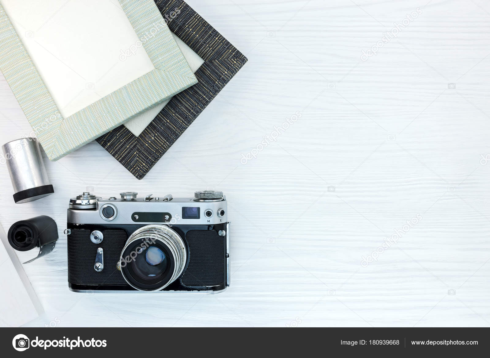 old retro camera and empty photo frames on white wooden background ...