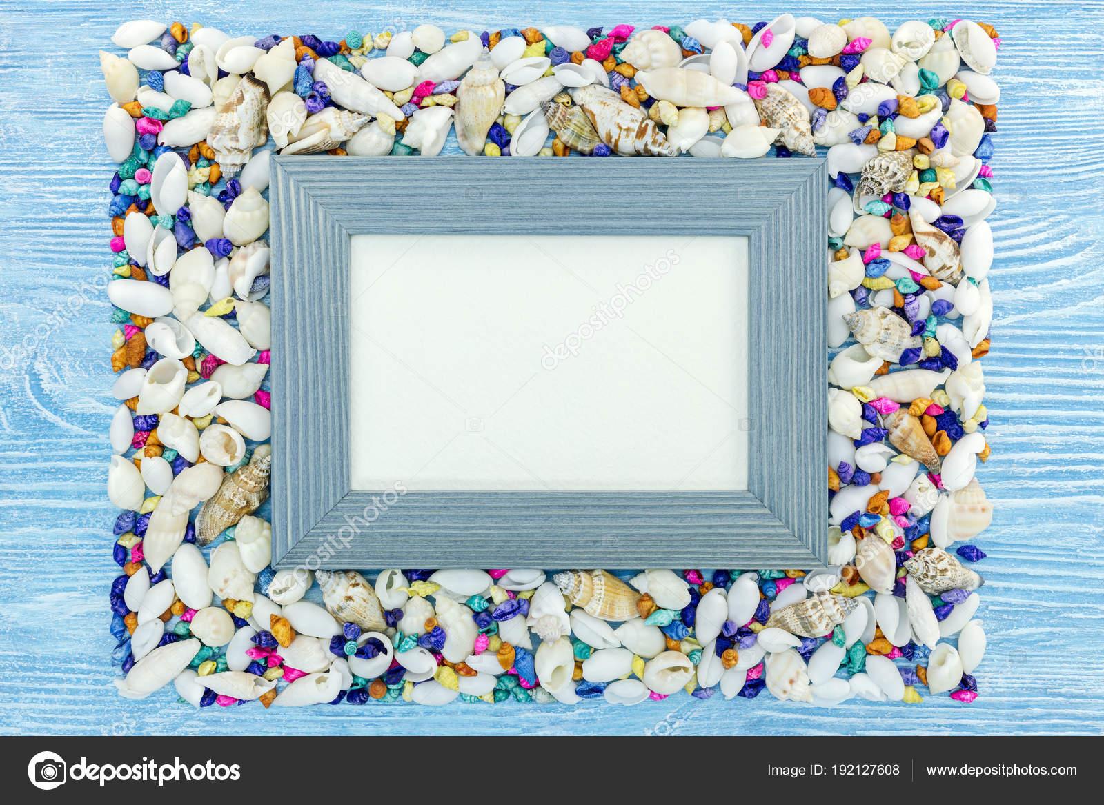 marco vacío sobre fondo azul madera con conchas multicolores — Foto ...