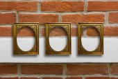 Fotografie Gilded wooden frames for pictures on old brick wall