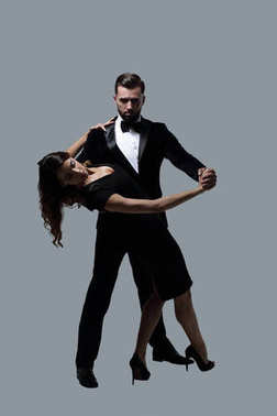 Portrait Of Young Couple Dancing Over Grey Background
