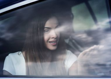 young woman portrait in the car behind the window