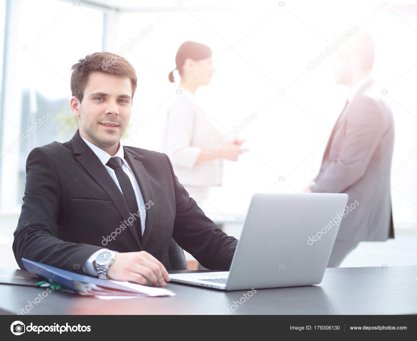 Successful Businessman Sitting Behind A Desk With An Open