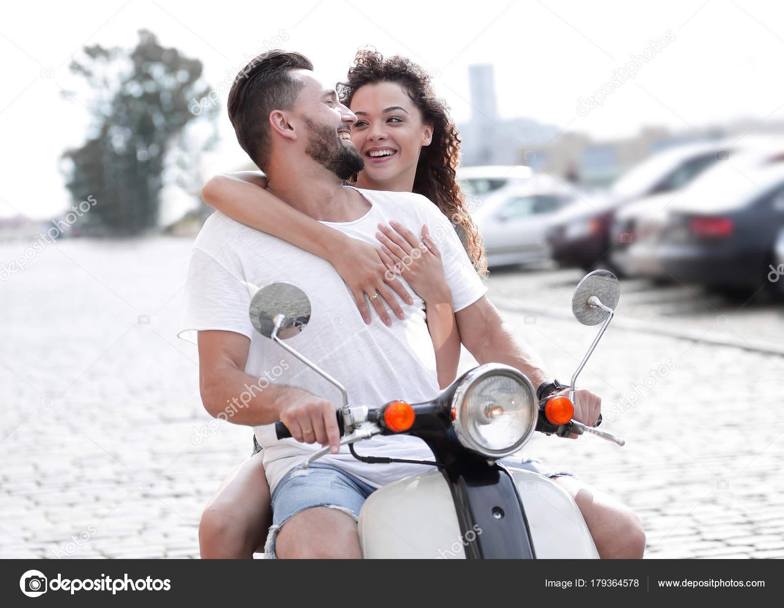 1c0b8cf587a Feliz pareja joven montando una moto en la ciudad en un día soleado — Foto  de