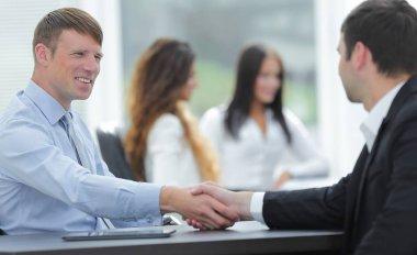 handshake business partners at your Desk