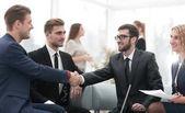 partneři uzavřít dohodu a potřesení rukou za přítomnosti členů týmu