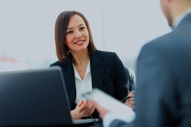 Beautiful young businesswoman conducting a job interview seated at her desk.