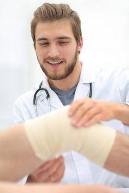 traumatologist examining the bandage on his knee.