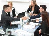 üzleti partnerek az íróasztalnál ülve kézfogás