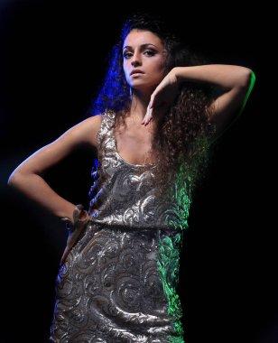 brunette woman in dance position, studio dark background