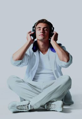 Portrait of a relaxed young man listening to music on headphone against white background.
