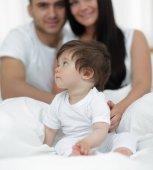 Fotografie glückliches Paar und Sohn sitzen im Bett