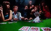 Fotografie elegantní muž v černém obleku záhyby dvě karty v kasino poker v las vegas nad černou