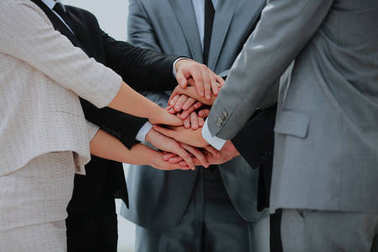 Business team joining hands together.