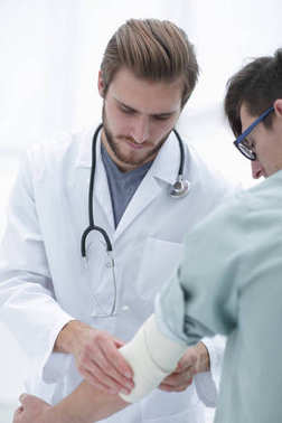 Orthopedist applying bandage onto patients arm