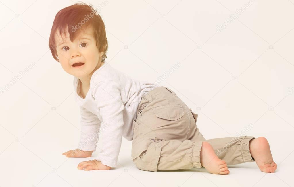Portrait of a cute sweet baby crawling in the studio