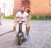 Fotografie Mladý pár jezdecké skútr v městě