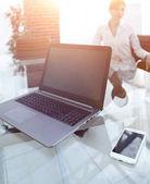 Fényképek laptop és okostelefon egy üzletember asztalán