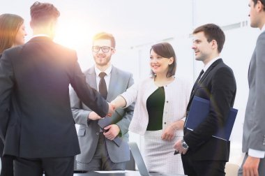 handshake of business partners standing next to their lawyers