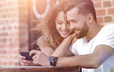 Happy loving  couple using a smartphone sitting in terrace