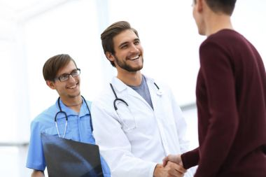 smiling doctor shaking hand of a patient