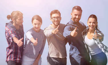 smiling group of young people showing thumb up.