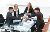 Fotografie handshake obchodních partnerů sedí u stolu