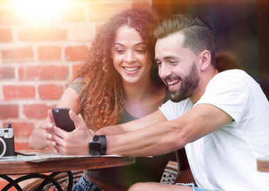 Lovely young couple looking at smart phone at cafe
