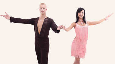Two young ballroom dancers in studio  against  white background