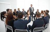 Fotografie zkušený kouč klade otázky pro účastníky školení
