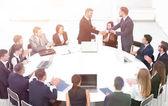 Geschäftspartner geben sich bei den Gesprächen am runden Tisch die Hand