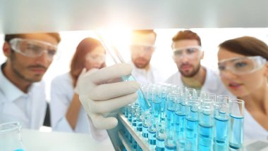 background image is a group of microbiologists studying the liqu