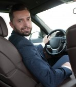 businessman sitting at the wheel of a prestigious car