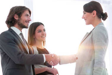 Business partners handshaking over business objects on workplace stock vector