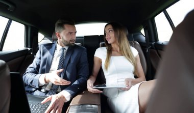 successful people working together in back seat of car