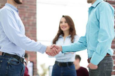 Handshake between businesspeople in a modern office.