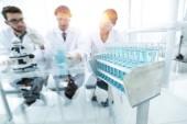 Fotografia immagine di sfondo degli scienziati che studiano il liquido blu in una boccetta