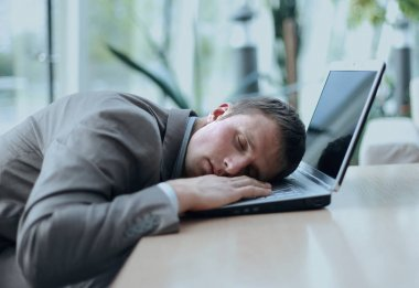 A tired business man sleeping on his laptop at the office