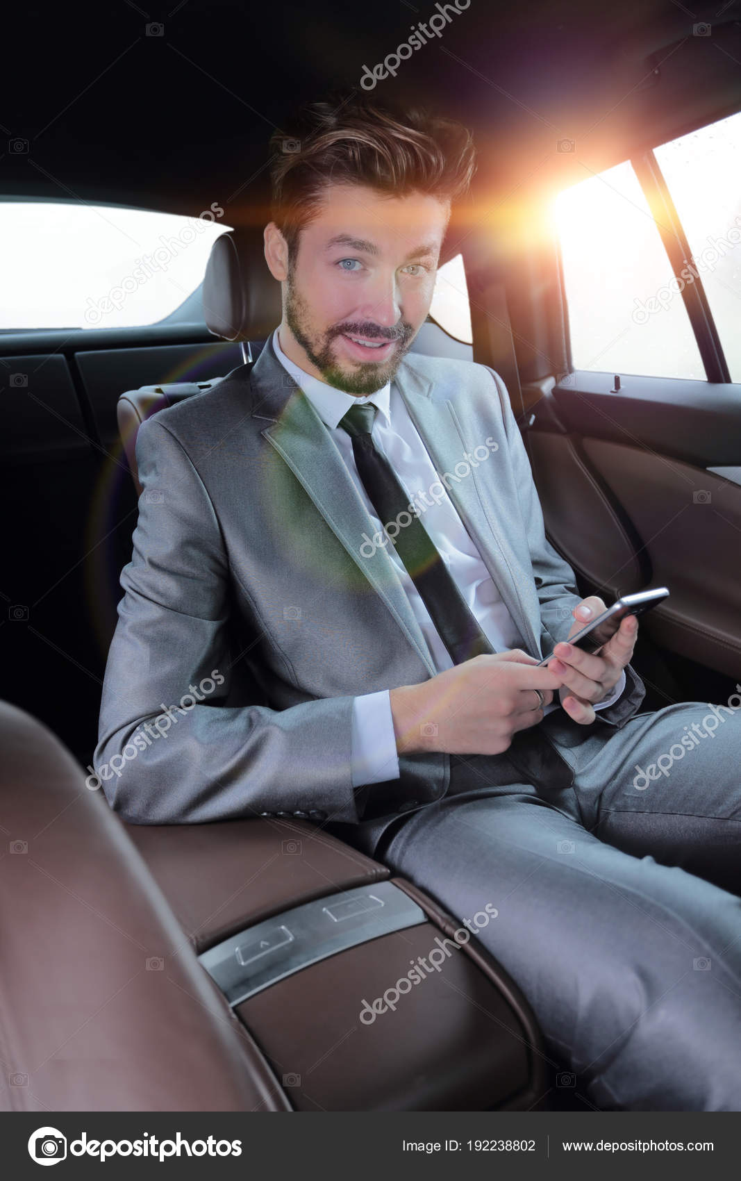 man in suit sitting in car and reading messages on smartphone ...