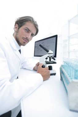 Student in biology using microscope in training class