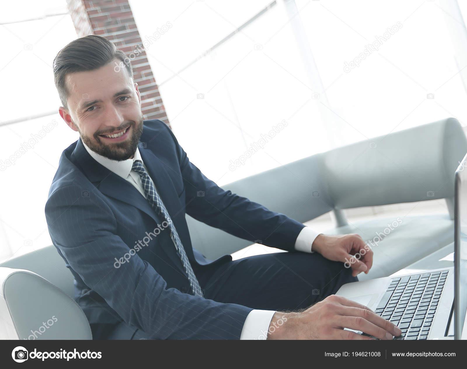 Homme moderne travaillant sur ordinateur portable dans le hall d