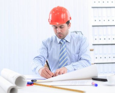 Architect looking working in office at desk. Wearing hardhat and taking notes on paper stock vector