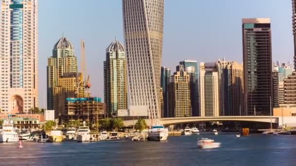 Timelapse view of Dubai Marina skyscrapers with floating yachts and boats , United Arab Emirates